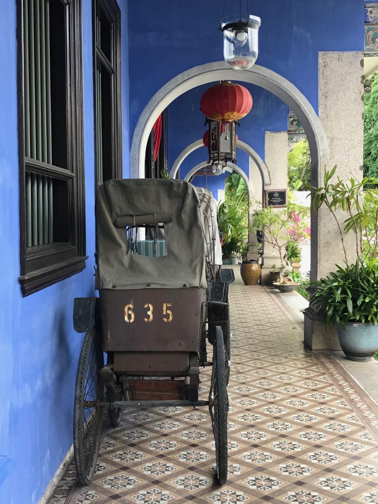 Antique trishaws and the blue facade of the blue mansion