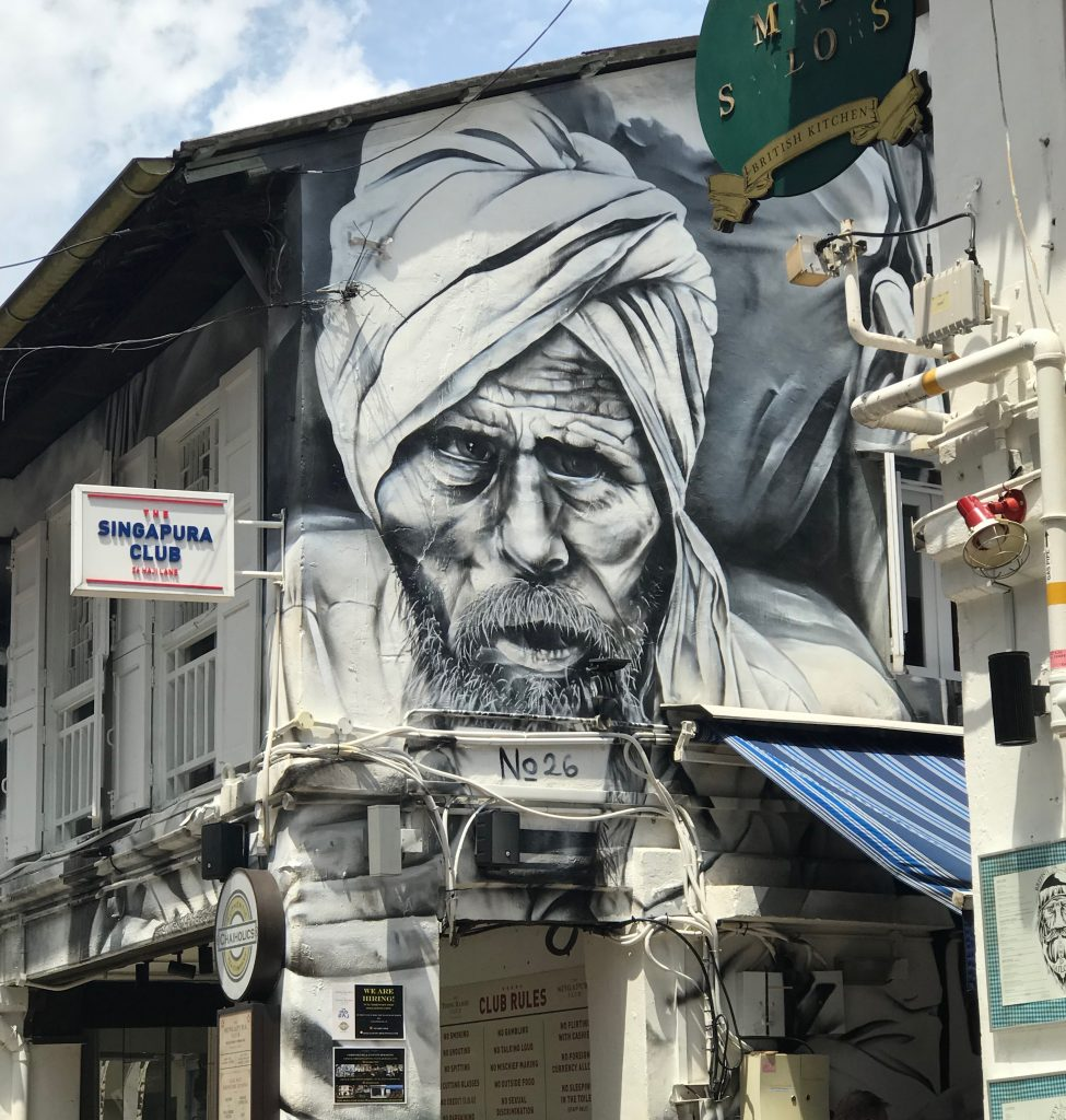 A mural painted of a man in a turban on the side of a building