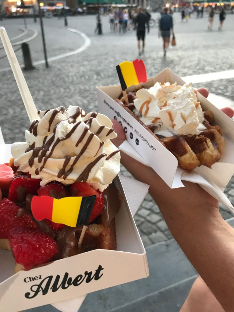 waffles covered in strawberries, cream and chocolate sauce with a Belgium paper flag on top