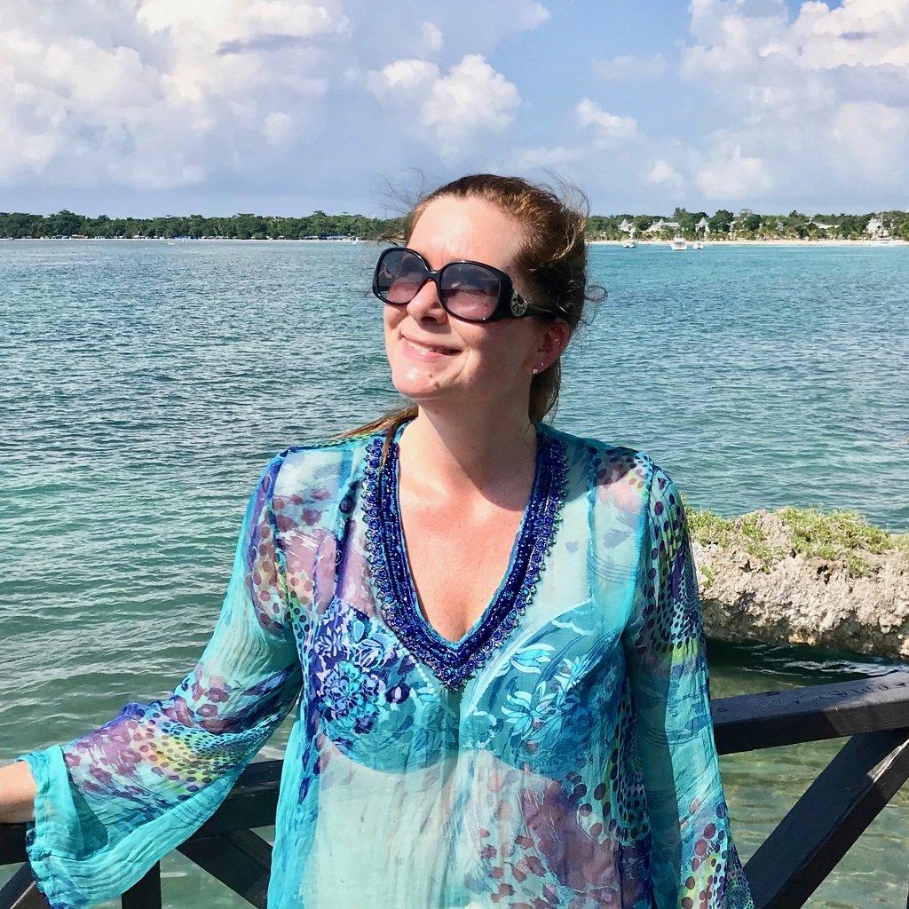 A woman wearing a blue kaftan on a beach in Dubai