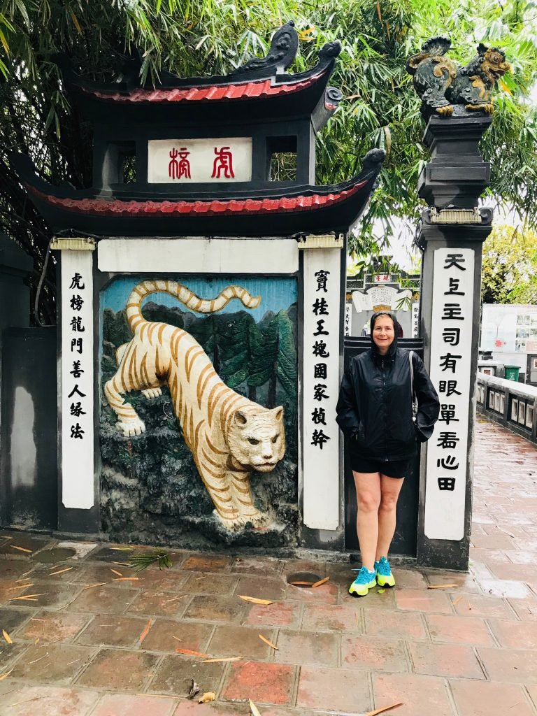 Angela standing beside an entrance with a tiger statue