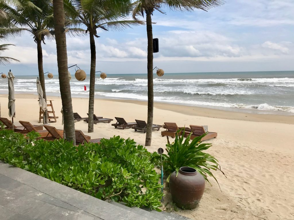 Naman Retreat beach with loungers and lined with palm trees