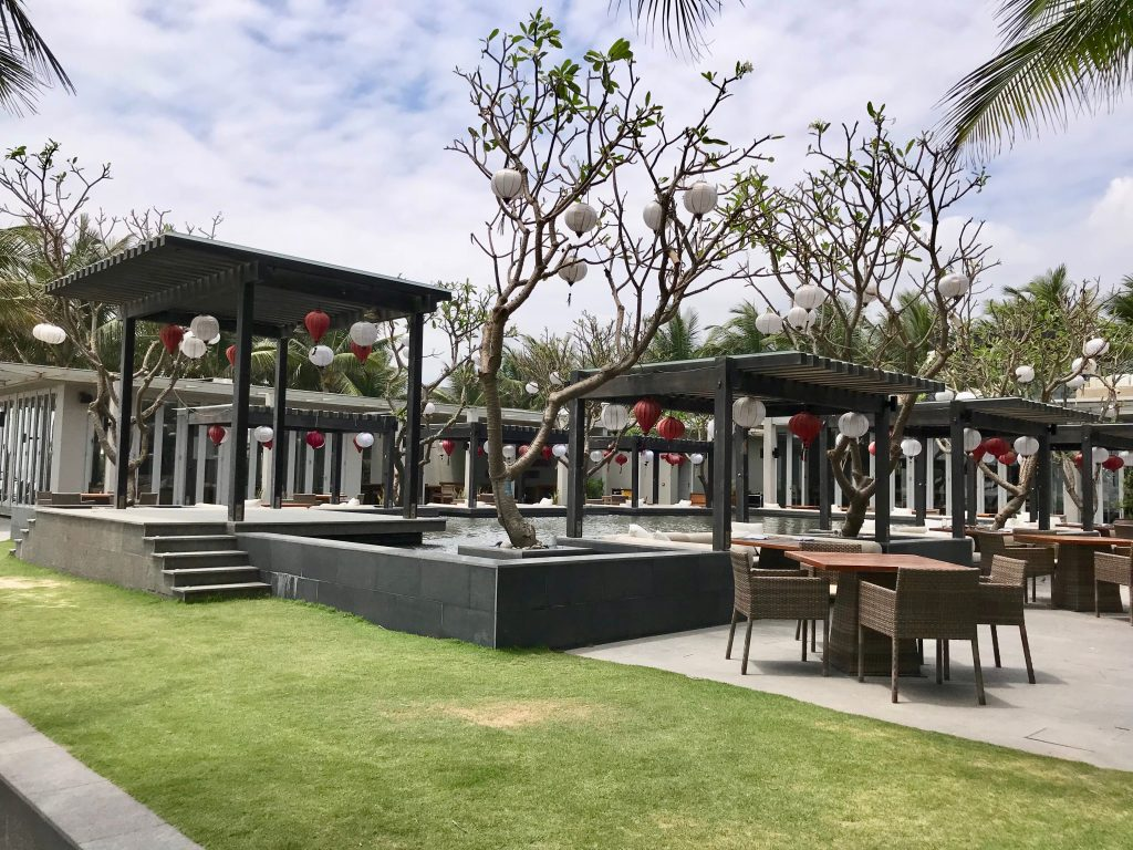 Outside area with day beds and hanging lanterns in Naman Retreat