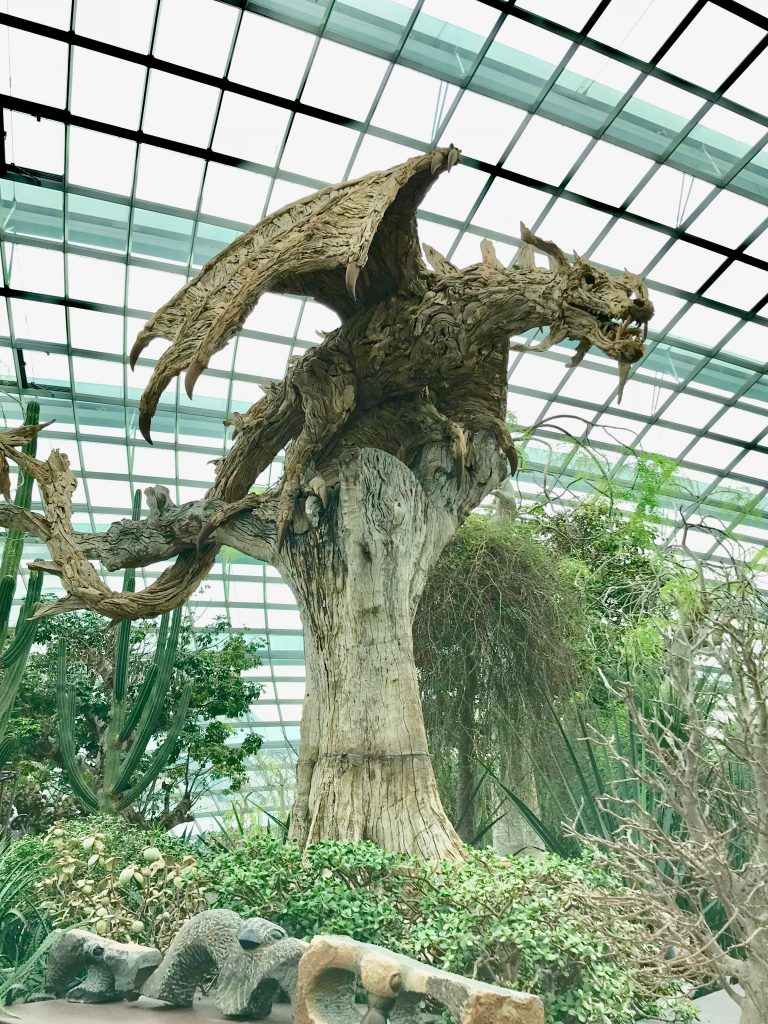 A wooden dragon perched on a tree stump in Singapore's biosphere