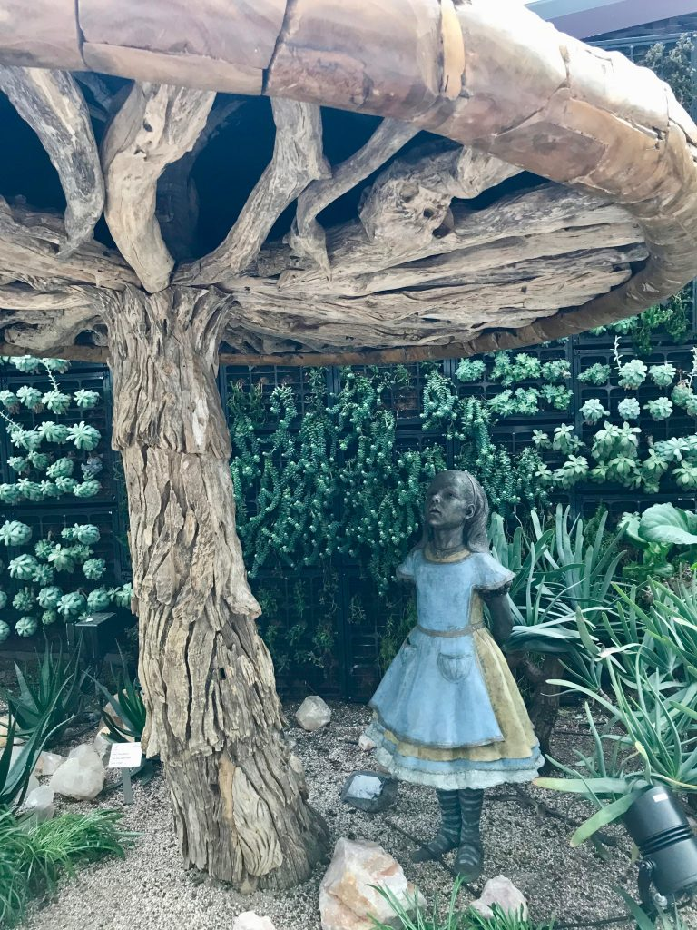A wooden Alice in Wonderland beneath a wooden mushroom on display in Singapore's biosphere
