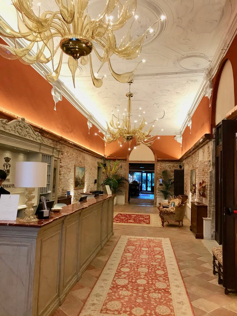 entrance hall to the hotel with orange painted walls and two elaborate glass chandeliers