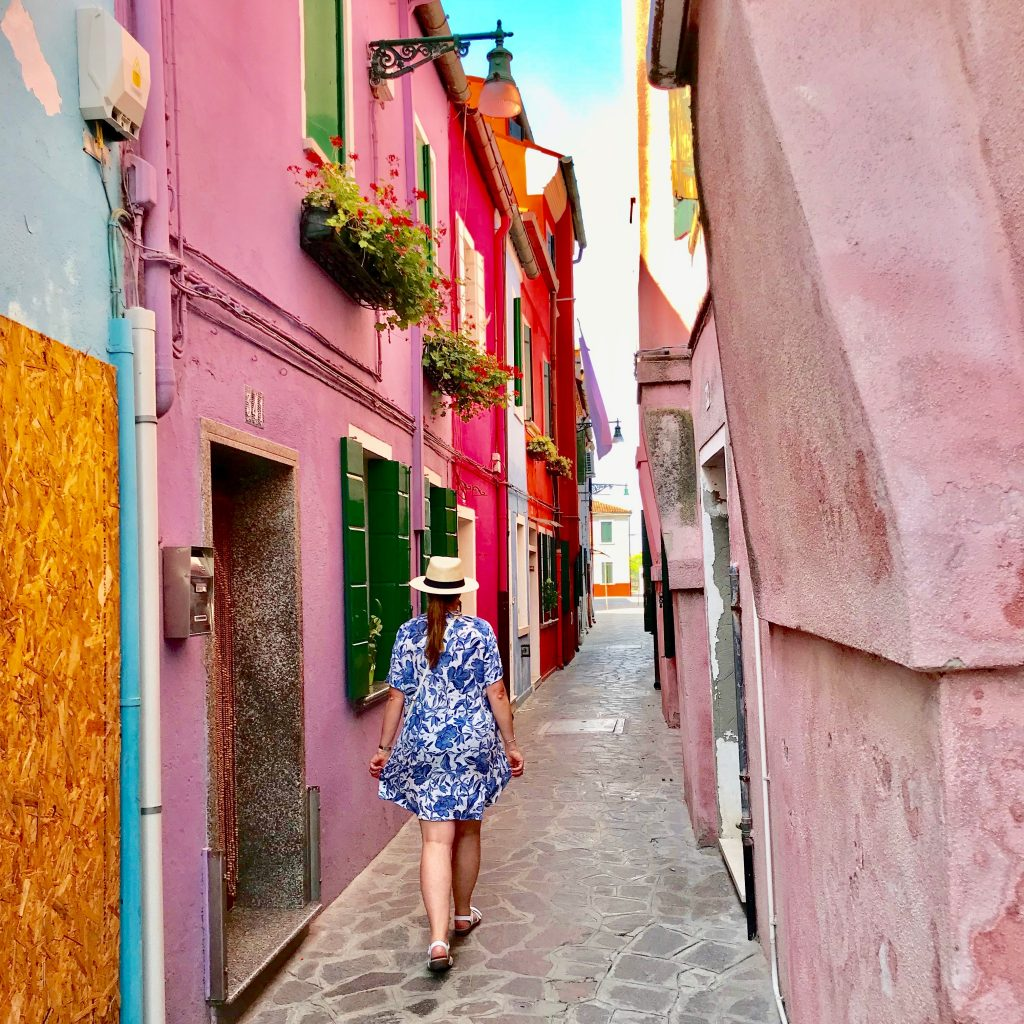 A photo of me walking along a narrow alleyway in Burano