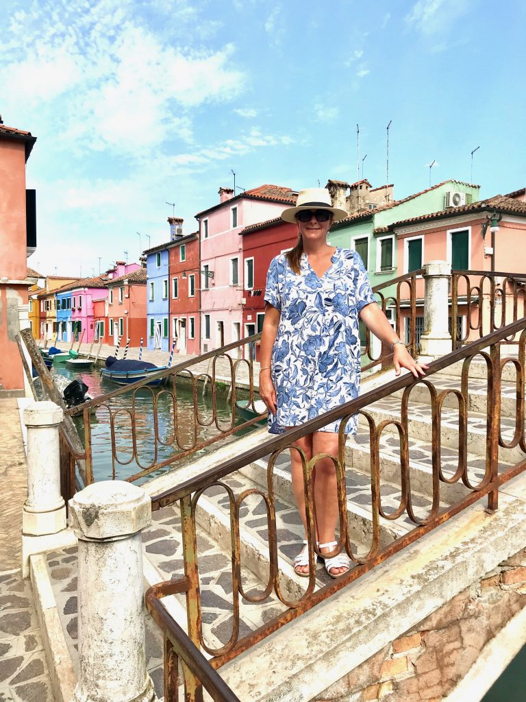 A bridge in Burano across a canal showing me standing on it