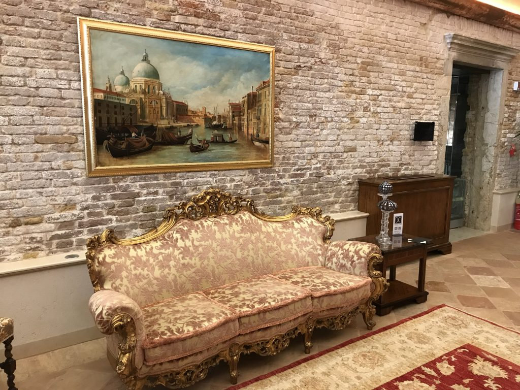 A ornate two-seat sofa with an oil painting of a Venice canal above