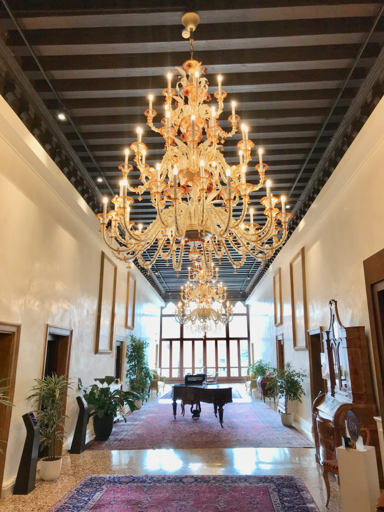 the hotel landing with a huge glass chandelier and antique furniture.