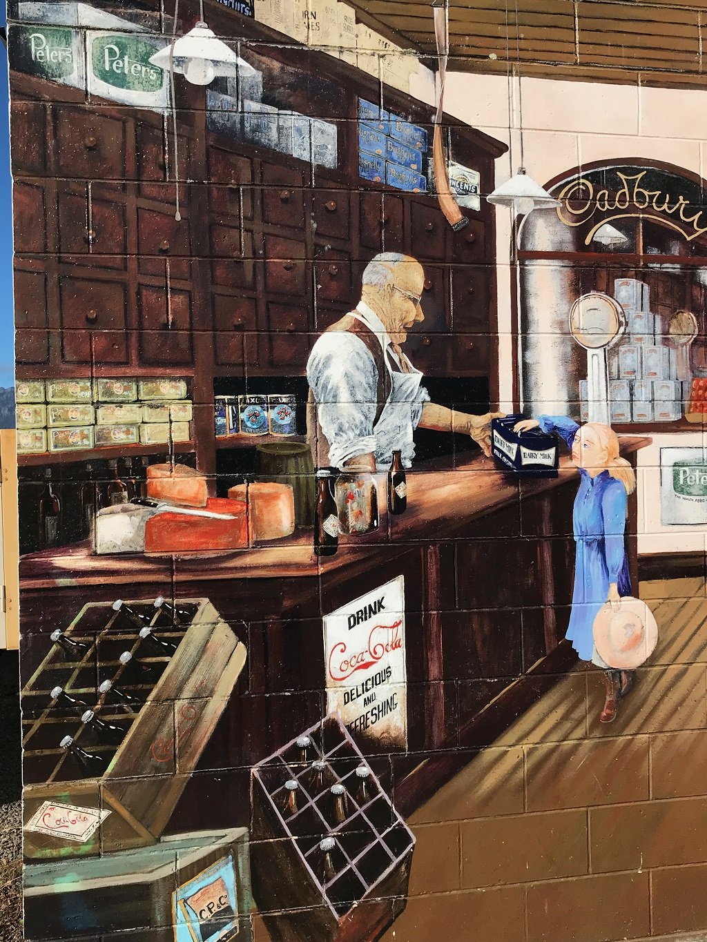 The mural of a shopkeeper serving a girl with two of the world's most famous brands on show. Painted straight on brickwork gave this one a tiled appearance.