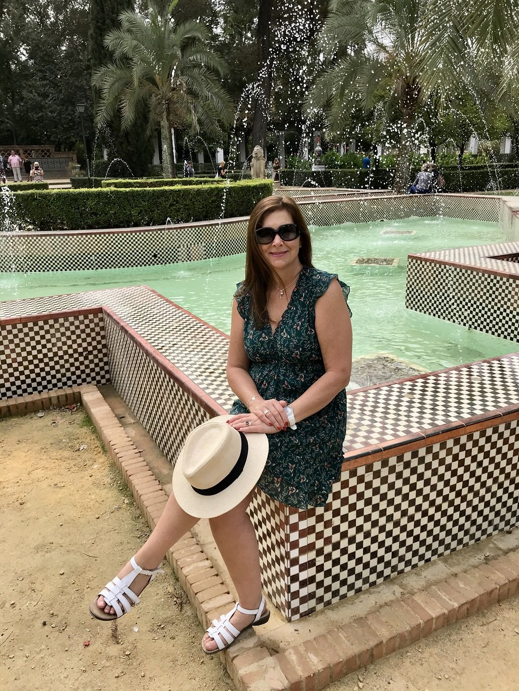 A woman sitting on the corner wall of a fountain in the Maria Luisa Park.