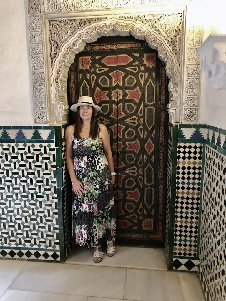 Angie standing by a highly ornate and colourful door inside the Alcazar Al Real