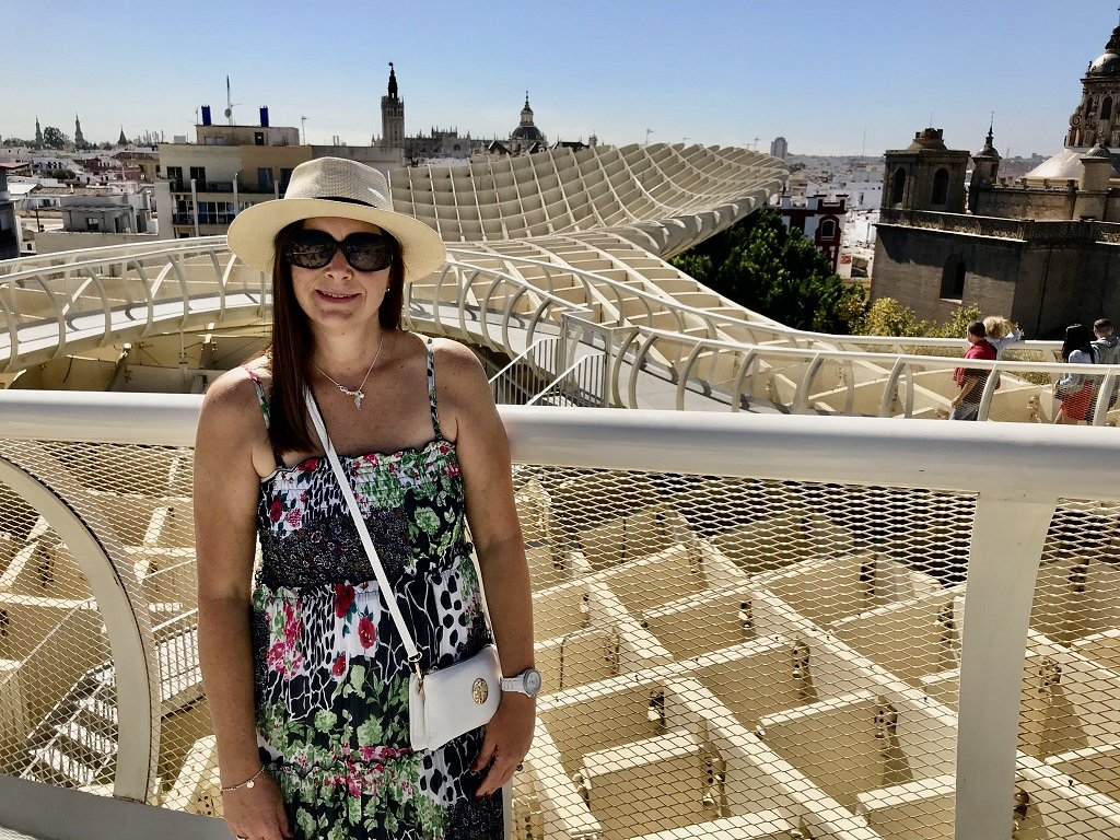 A woman standing on the walkway of the Metropol Parasol wooden structure in Seville