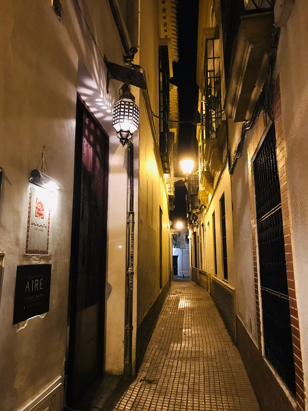 The narrow street leading to Aire Ancient Baths lit up by wall lights at night