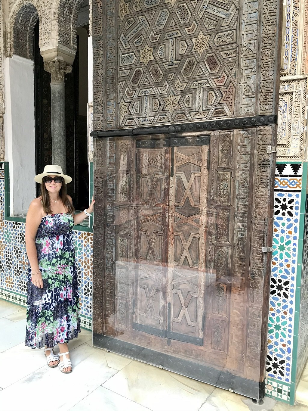 A woman standing by a large Moorish wooden door in the Alcazar