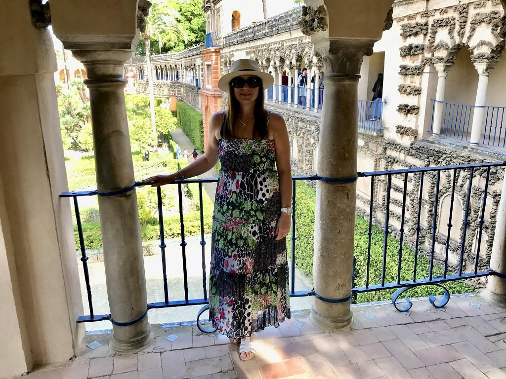 A woman standing on theBalcony in the Alcazar with the gardens behind her