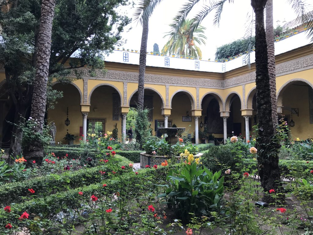 A view of the arched columns of the courtyard with pretty planting in front of them