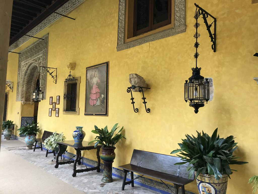 Yellow walls of the garden courtyard lined with antique Spanish objects like lamps and portraits