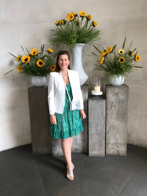 A woman wearing a green knee length dress and a white jacket in Dubai