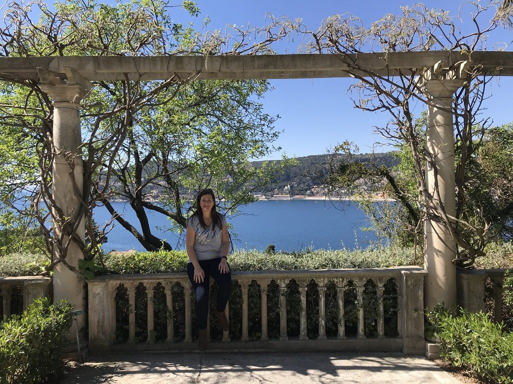 A woman sitting on a balustrade with a view of Cap Ferrat