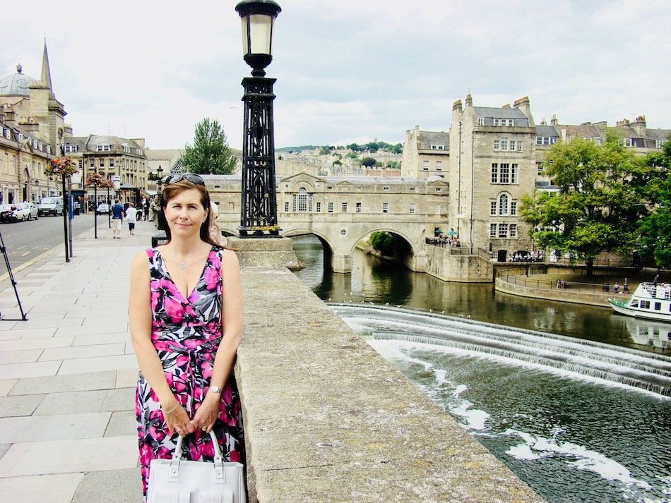 A lady standing beside a river in Bath
