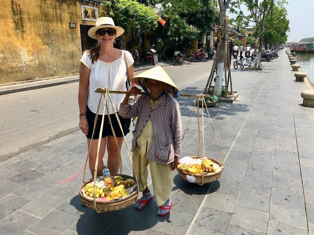 A photo of me standing next to a small lady selling bananas in Hoi An