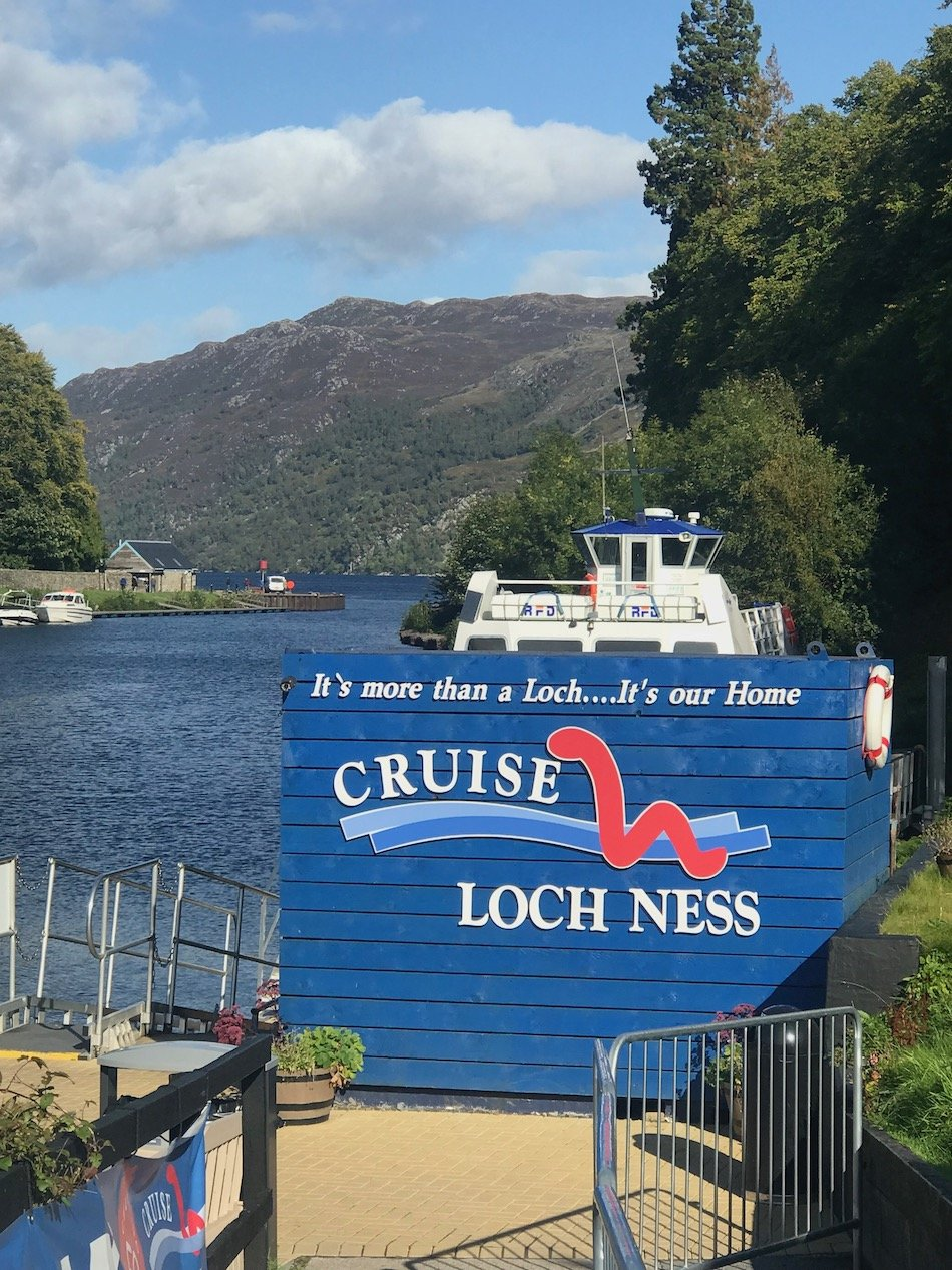 Cruise Loch Ness sign with the water behind it