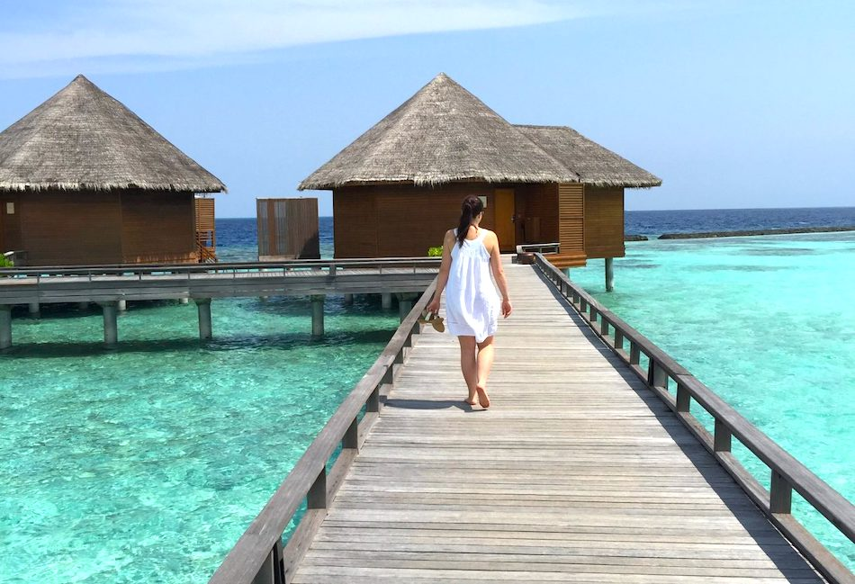 a woman walking towards an overwater villa