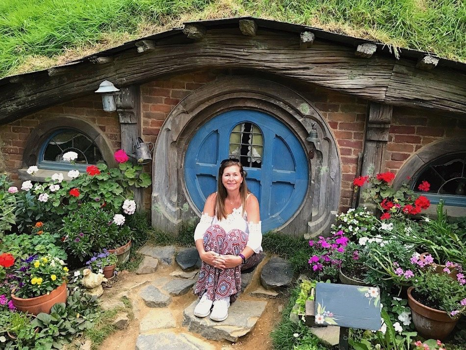 Lady sitting outside a hobbit house with a blue door