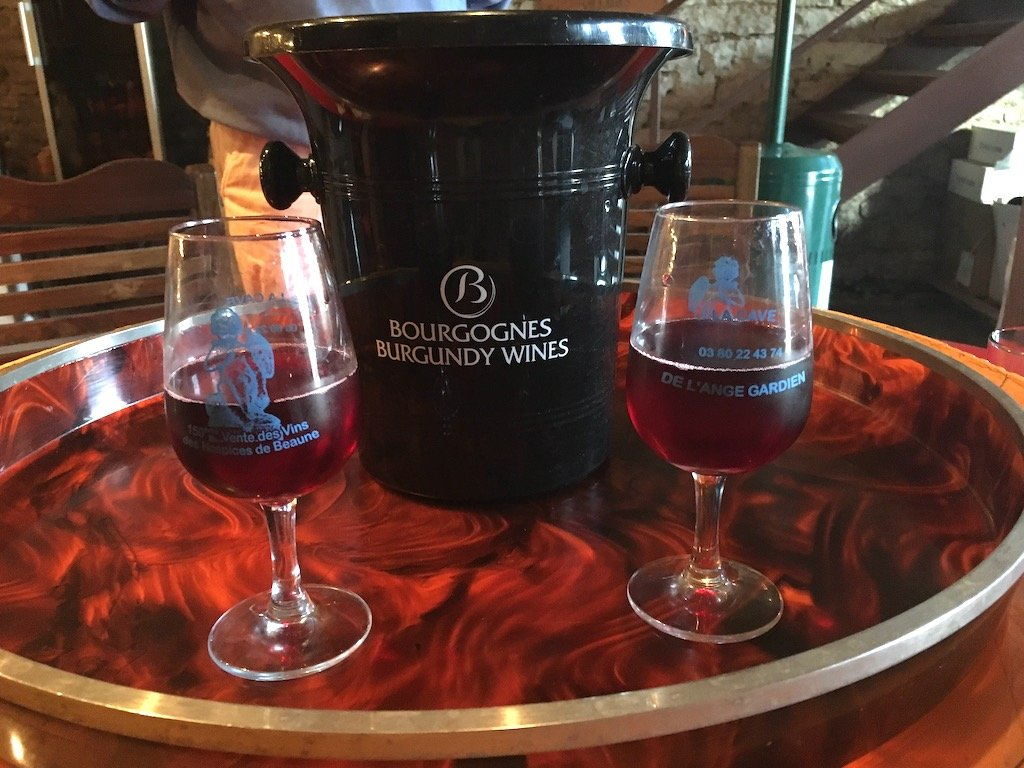 two glasses and a bottle of Burgundy red wine on a tray