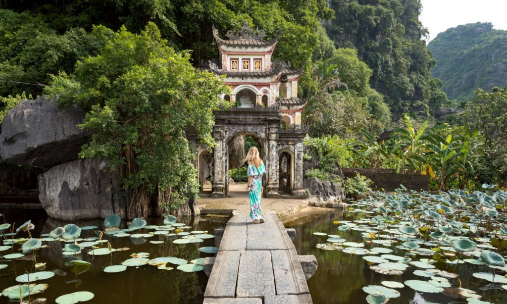lady walking to a temple near water in Tam Coc