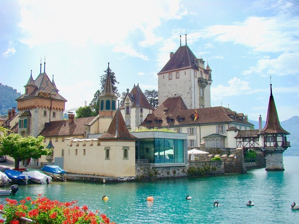 Oberhofen Castle sitting on the edge of Lake Thun in Switzerland