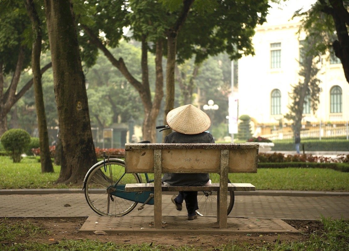 Person sitting on a park bench with conical Vietnamese hat