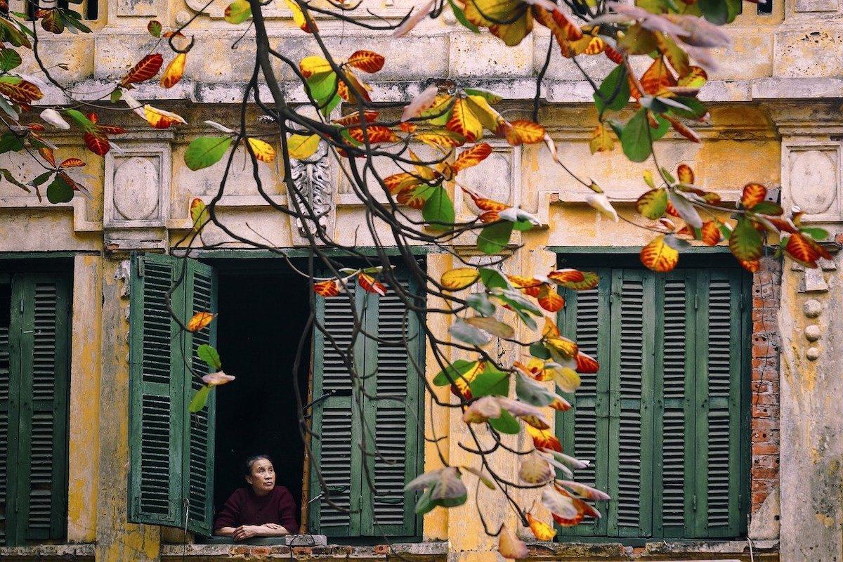 Vietnamese lady looking from her window in Hanoi