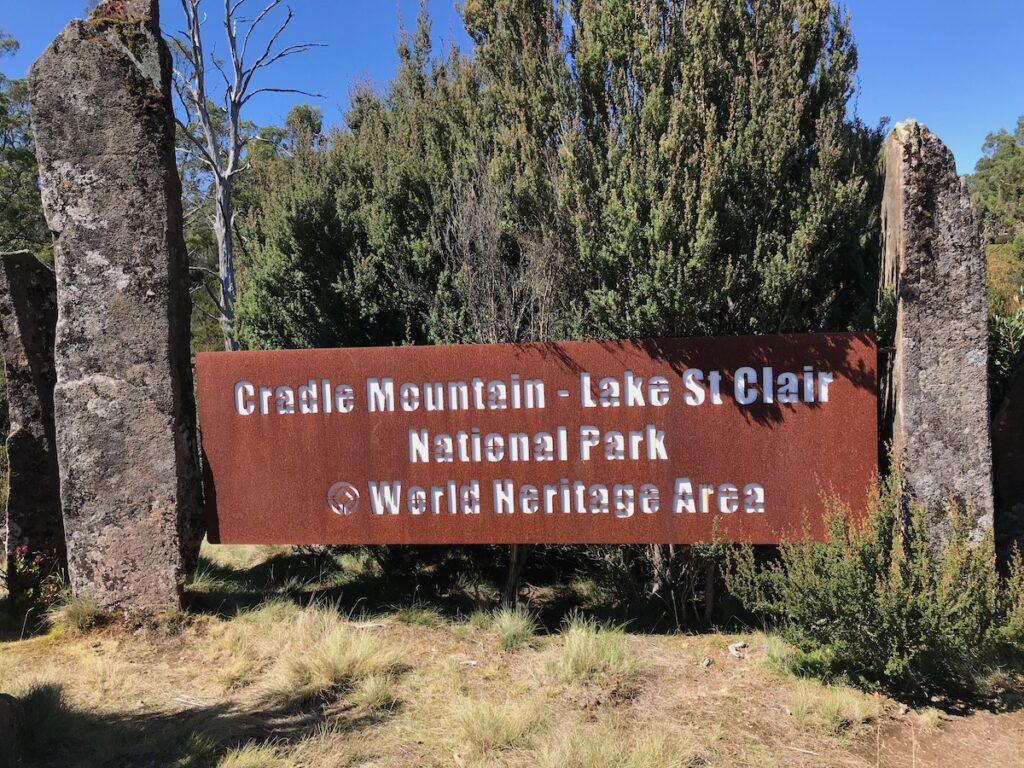 A weathered brown metal sign saying Cradle Mountain - Lake St Clair National Park @World Heritage Area