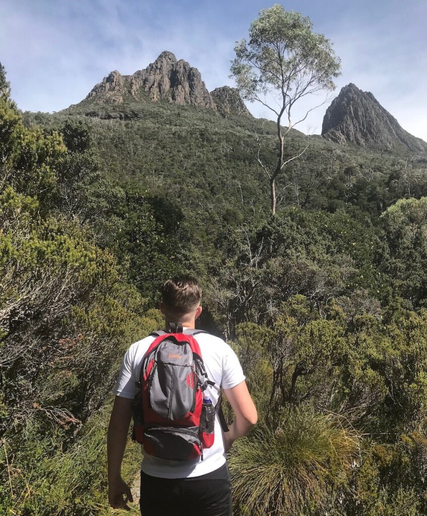 Dominic walking along the boardwalk with the two pinnacles of  Cradle Mountain looking above him