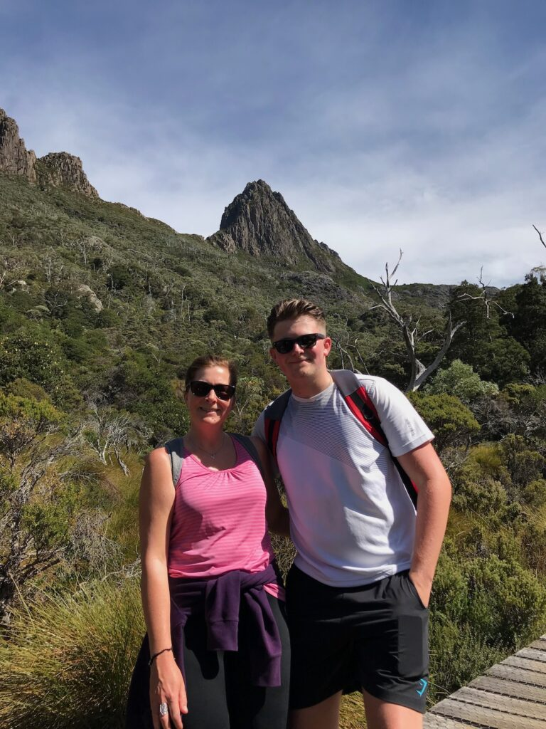 Angie wearing a pink top and Dominic wearing a grey t-shirt pose for a photo with Cradle Mountain in the distance