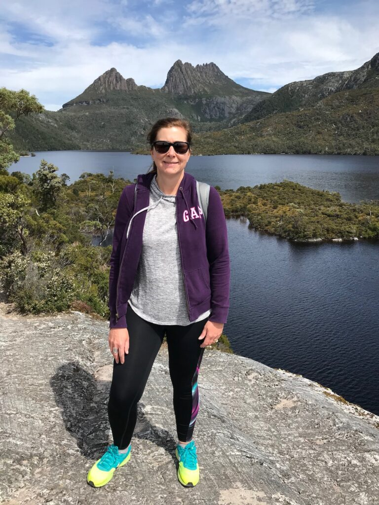 Angie dressed in a purple jumper and black leggings poses for a photo with the backdrop of Dove Lake and Cradle Mountain