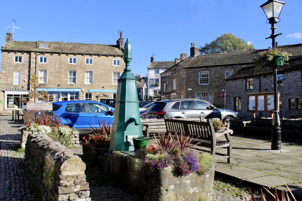 Grassington town square with a green pump with a bucket beneath as a focal point and surrounded by colourful flowers. Cars are parked nearby and stone built Yorkshire buildings surround the area.