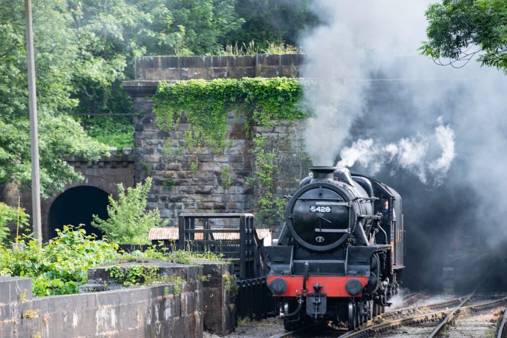 black and red steam train coming through the tunnel of a stone arch birch with smoke billowing from its chimney