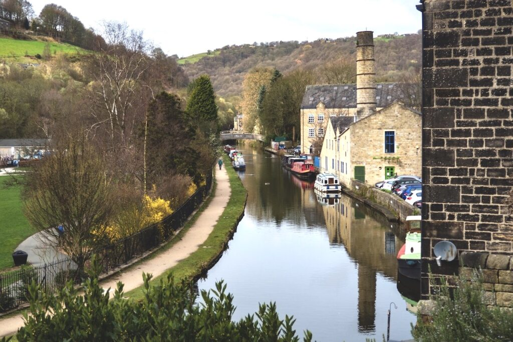 a view of the canal at Hebden Bridge in Yorkshire with parkland to the left and stone built industrial buildings to the right