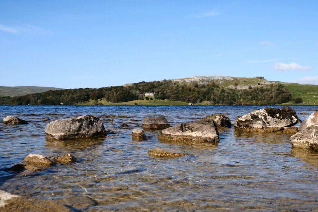 Water with large boulders in the foreshore and on the opposite side a green hill with a White House on the brow of the hill in Malham