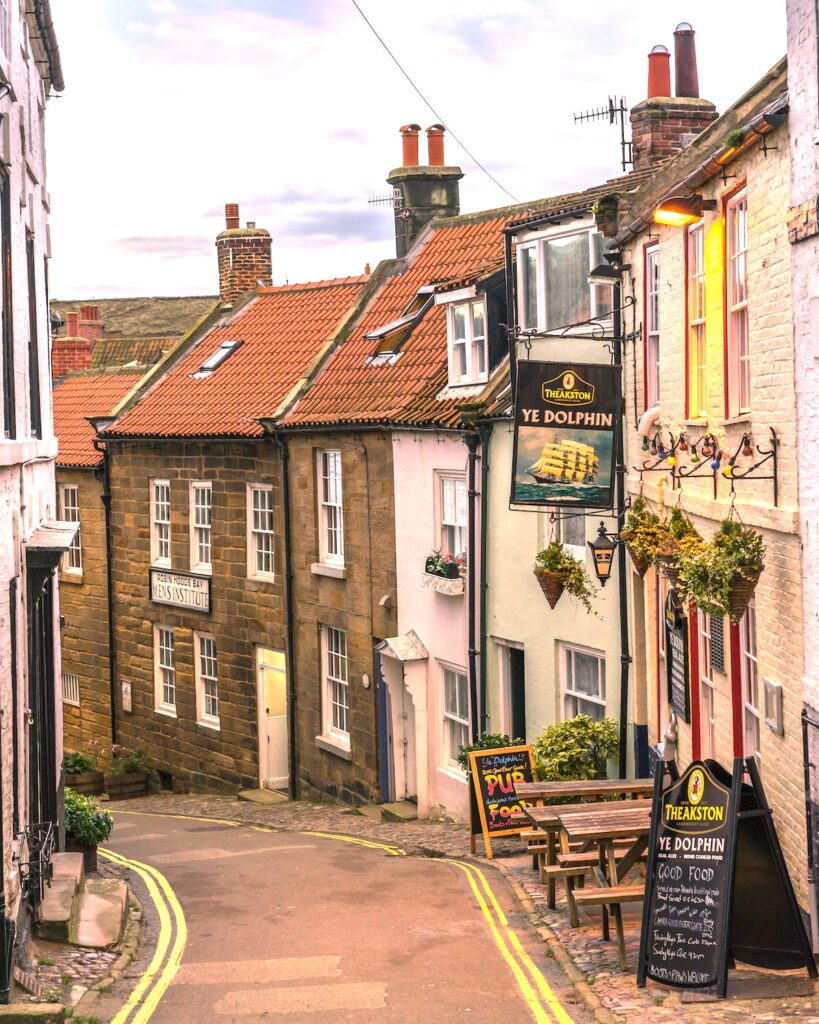 terraced cottages painted in pastel colours leading down a street in Robin Hood's Bay in Yorkshire. A pub sign saying Ye Dolphin hangs from one of the cottages