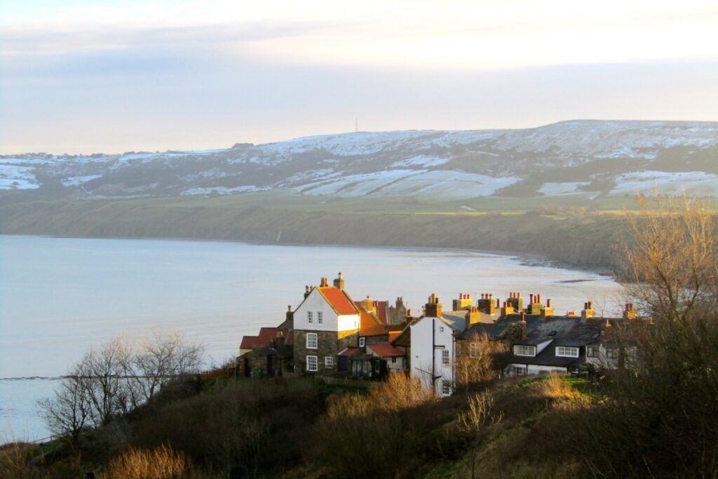 an aerial view of Robin Hood's Bay in Yorkshire. At the forefront are the towns houses sitting on a hill overlooking the North Sea. In the background are the Yorkshire Dales covered with a light dusting of snow