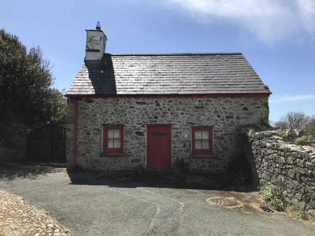 small stone house with a red door and window frames