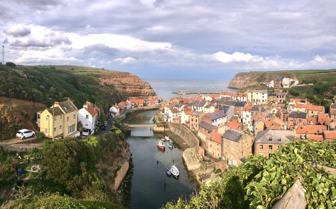 View across the rooftops and harbour at Staithes in Yorkshire and out to the sea