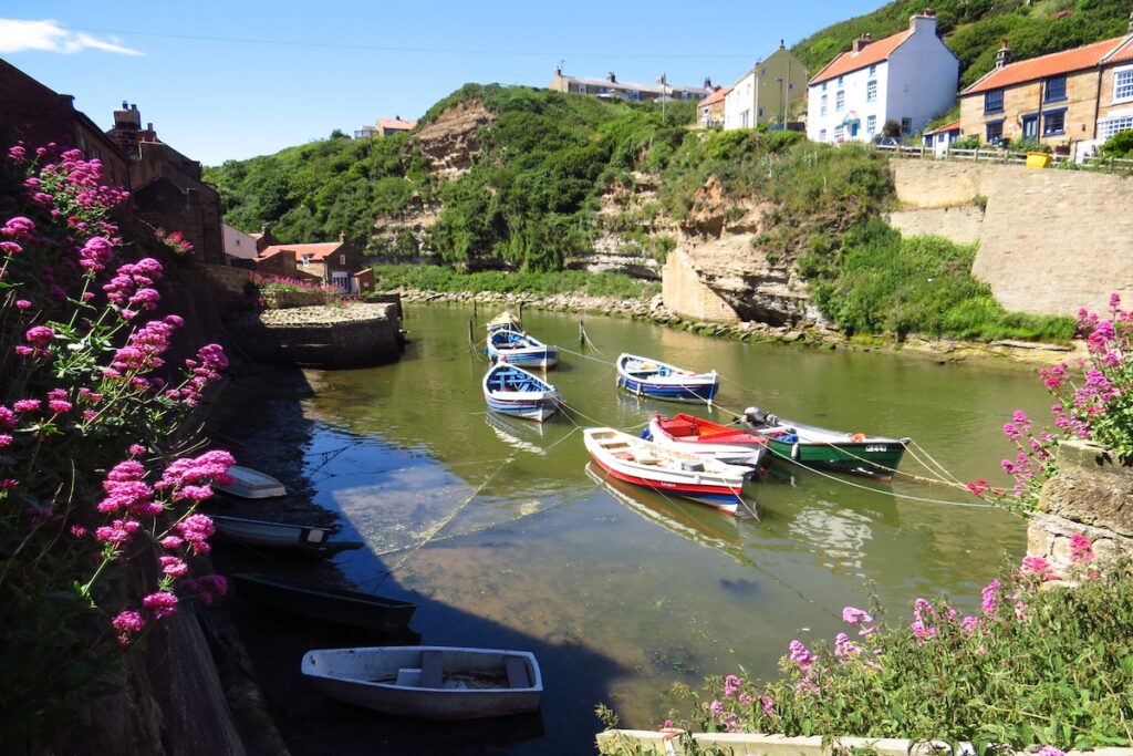 Staithes harbour in Yorkshire. seven coloured fishing boats are tethered in the water and cottages sit either side.