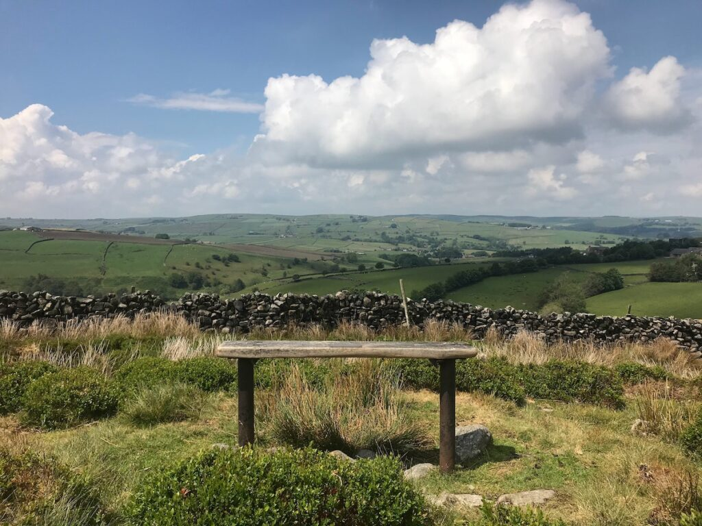wooden bench on a hill inferno of a stone flint wall with views across the Yorkshire countryside
