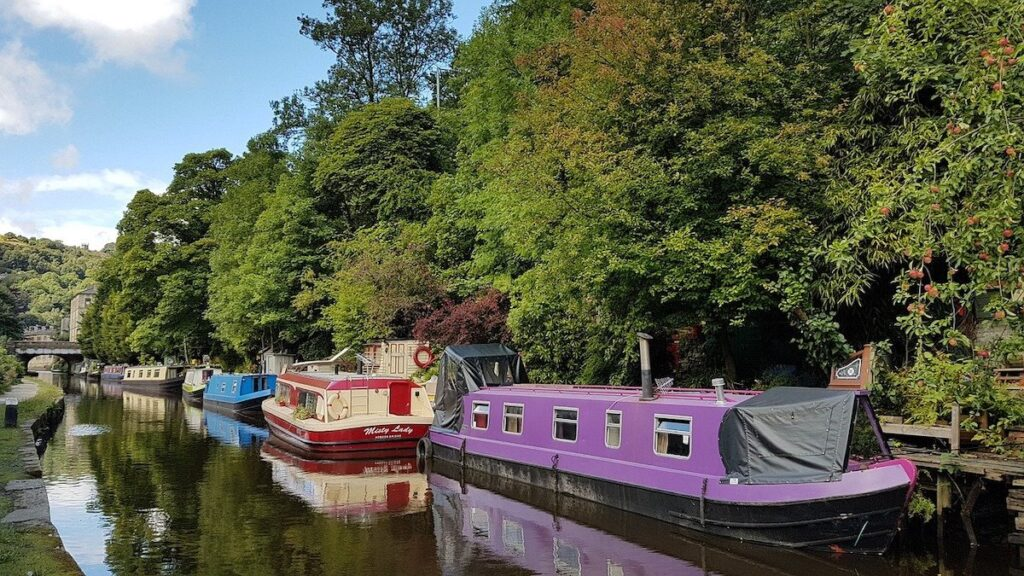 Pastel coloured canal boats tethered to the bank at Hebden Bridge canal Yorkshire